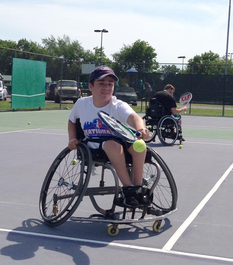 Young boy playing wheelchair tennis