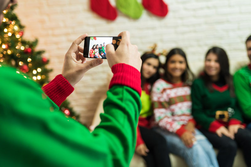 Person taking a photo of guests at a holiday party