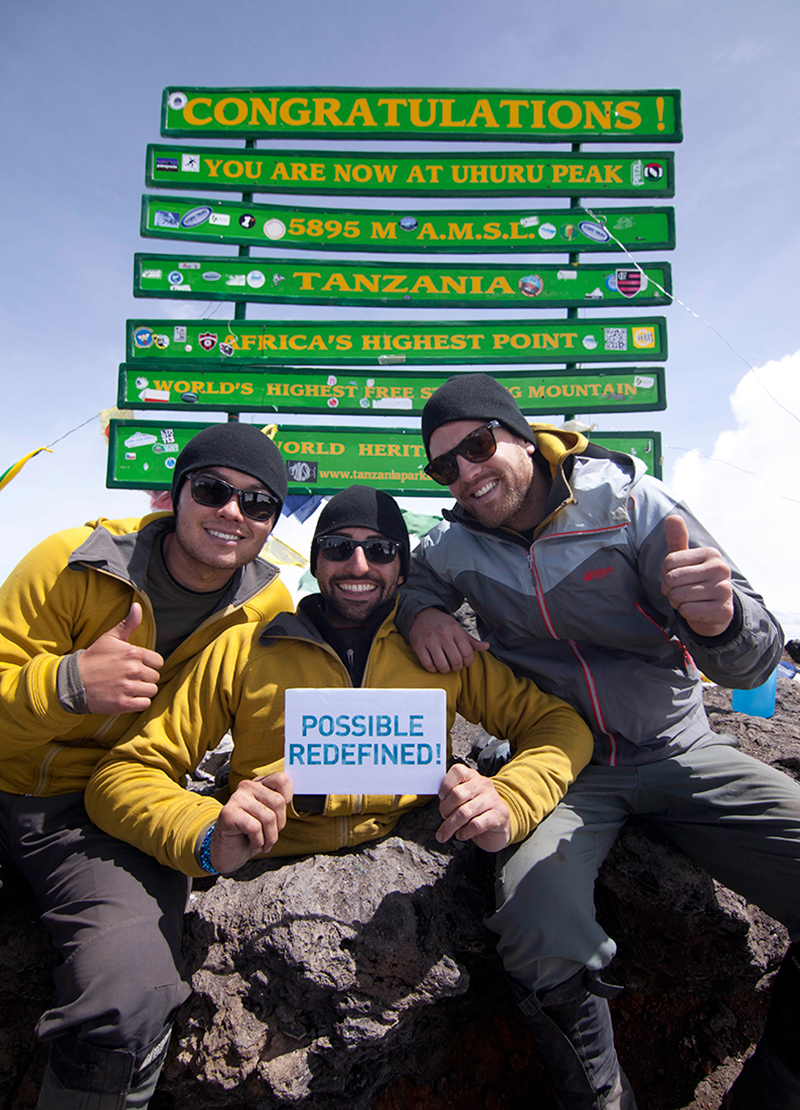 Spencer West with friends at the summit of Mt. Kilimanjaro