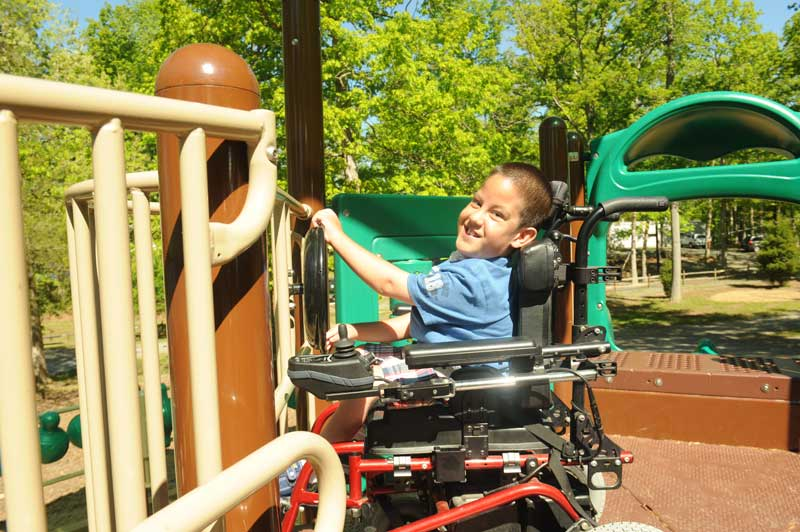 A child who uses a wheelchair enjoying an accessible playground