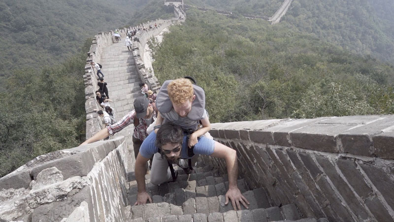 Kevan's friends carrying him up the Great Wall of China