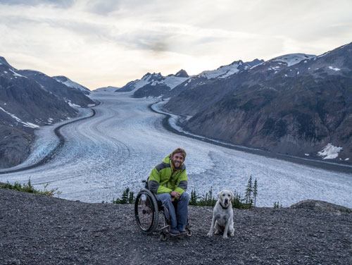 Kirk with his dog in front of an Alaskan glacier