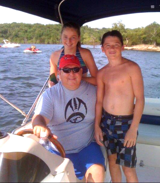 Bob boating with his kids on the lake
