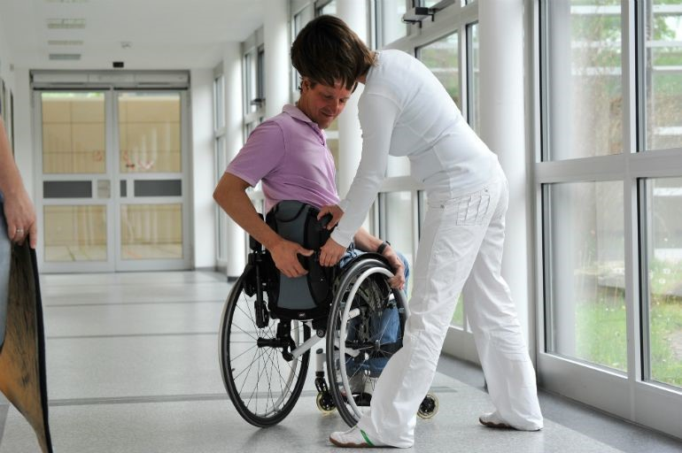 A man having his wheelchair checked over by a technician