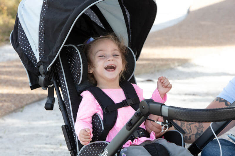 A smiling child in an early intervention adaptive stroller