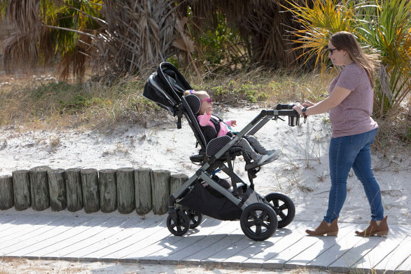 A woman strolling with her baby in an early intervention adaptive stroller