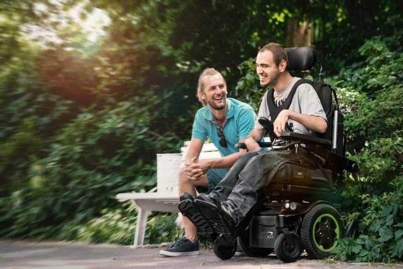 A man using a power wheelchair, hanging out with a friend
