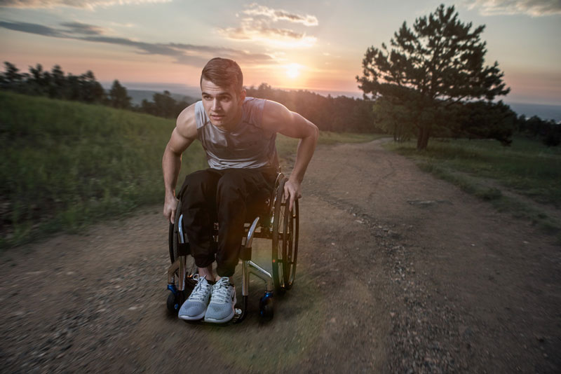 A man exercises outdoors in his wheelchair