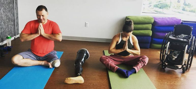 A woman who uses a wheelchair and a man with a leg amputation practice yoga together