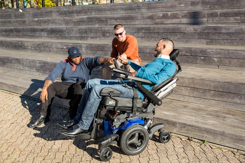 A man using a power wheelchair hanging out with his friends