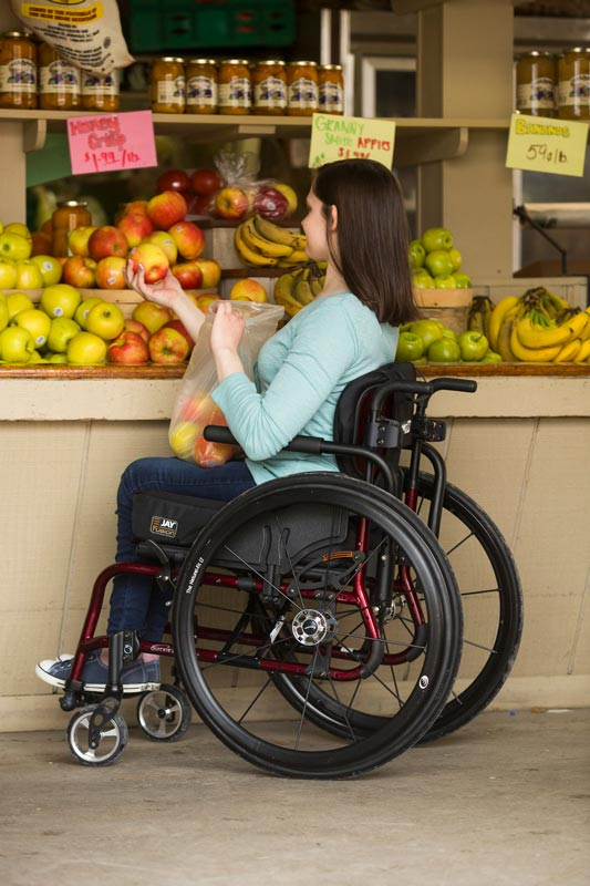 A woman using a wheelchair grocery shopping