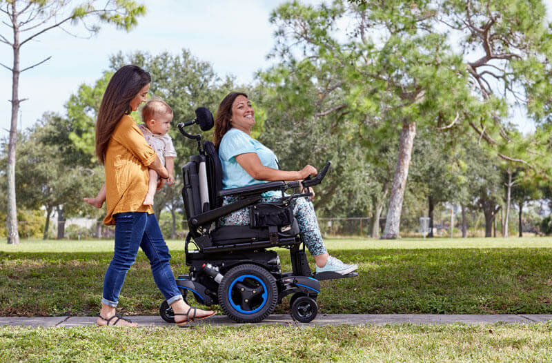 A woman using her power wheelchair with her family