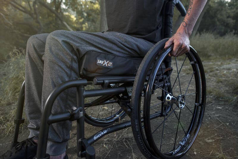 A man using a JAY X2 wheelchair cushion