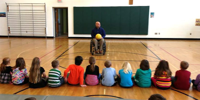 Greg teaching schoolchildren about wheelchair basketball