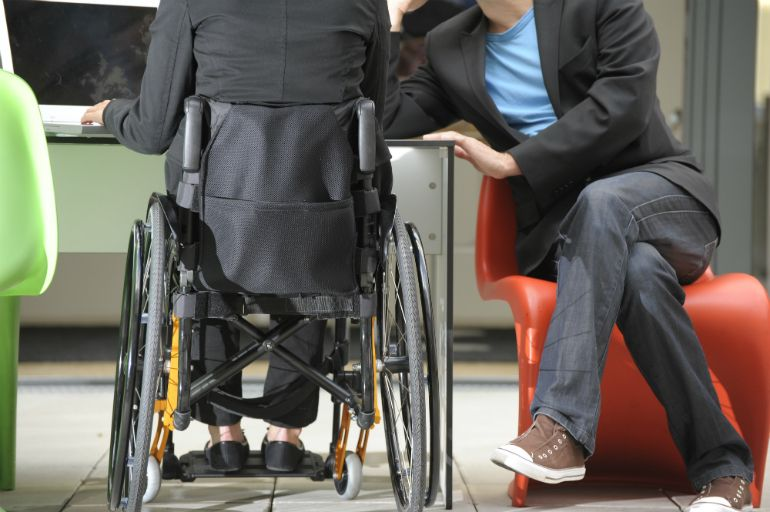 A person who uses a wheelchair working with an able-bodied colleague