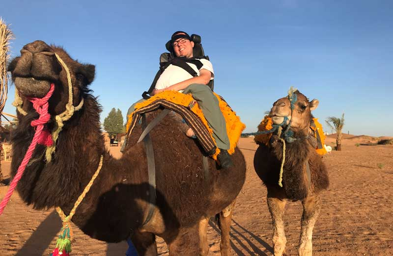 Cory riding a camel on a trip