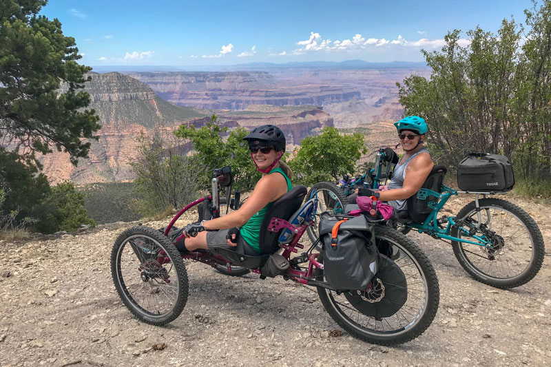 Two riders stopping for a photo with the Grand Canyon in the background