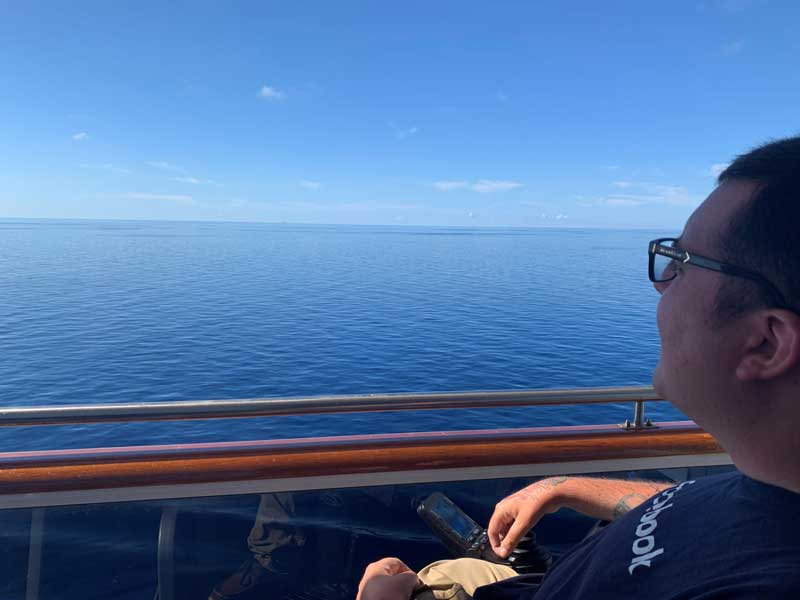 Cory Lee looking out over the ocean from the cruise ship