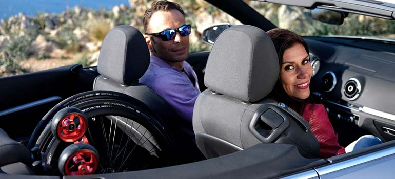 A man and woman in a convertible with a wheelchair in the backseat