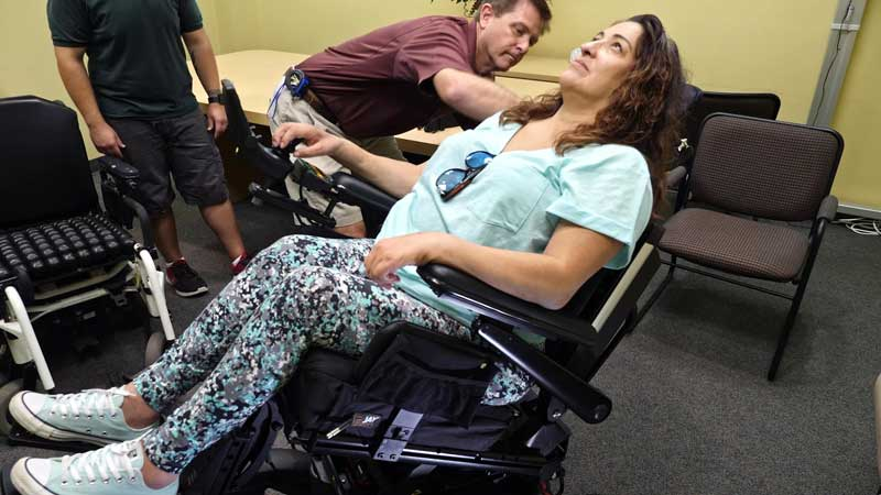 A woman testing new seating adjustments in her power wheelchair